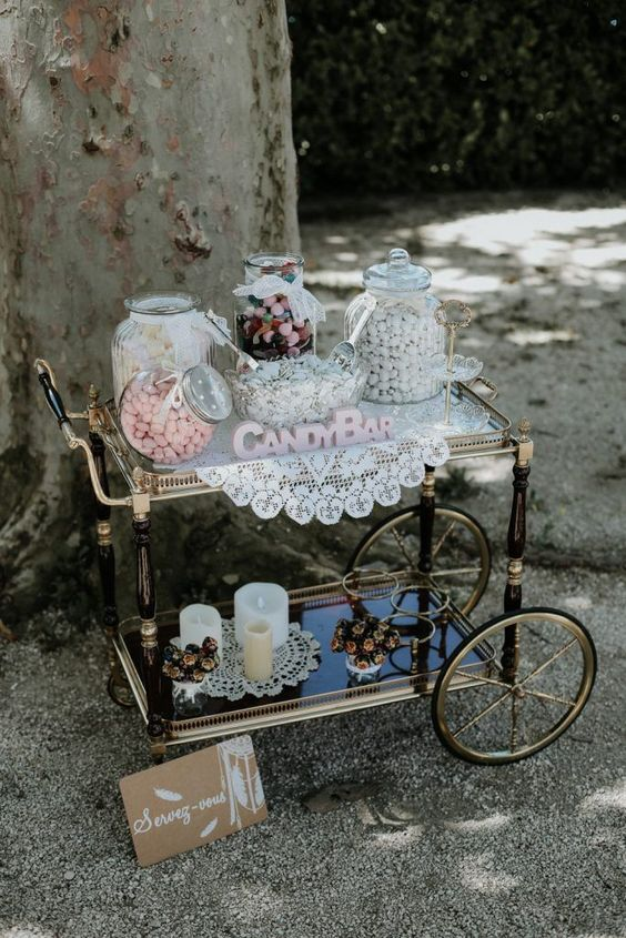 a chic vintage candy bar with an elegant vintage cart, a doily, candles, blooms and a sign for decor