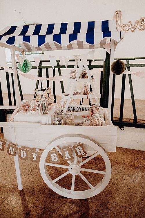 a chic white candy bar of a cart, banners, paper pompoms, lots of candies in jars is a very chic idea