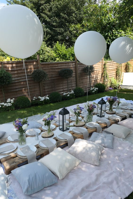 a chic white garden picnic setting with white blankets, neutral pillows, white balloons, bright blooms and a low pallet table
