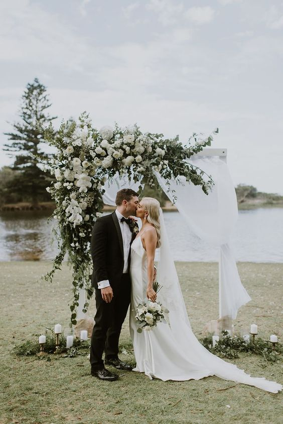 a classic weddign arch decorated with white fabric, greenery and white blooms and white candles on the ground