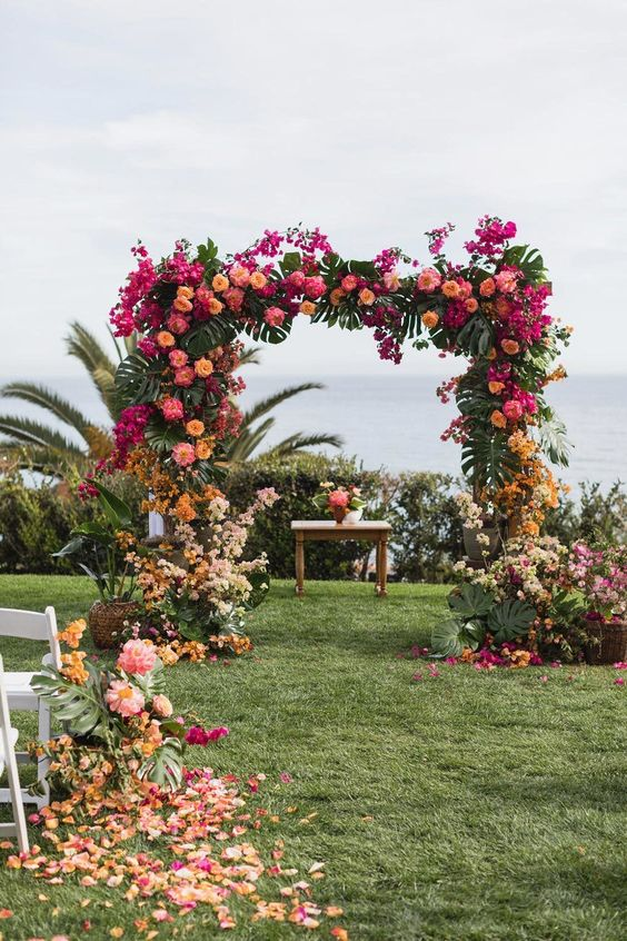 a color block wedding arch with tropical leaves, hot pink, orange, yellow and blush blooms for a tropical wedding