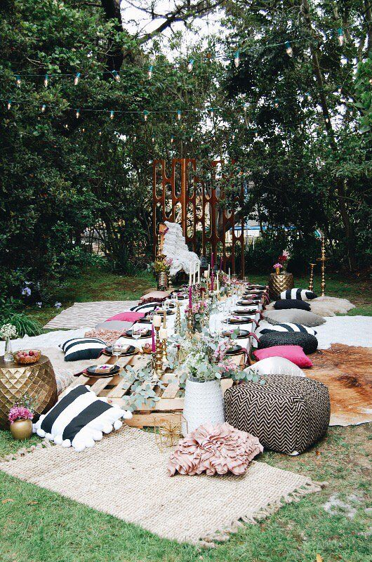 a colorful and glam picnic setting with pink blooms and greenery, colorful candles, colorful pillows and rugs