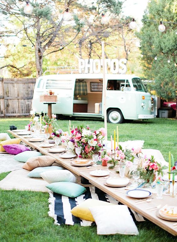 a colorful rehearsal boho picnic with bright pillows, rugs, blooms, candles in the backyard