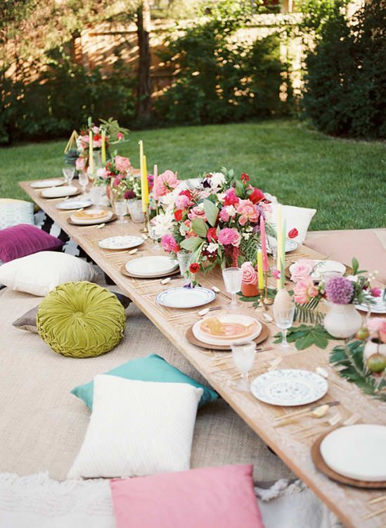 a colorful rehearsal picnic setting with bright blooms and candles, colorful pillows and porcelain