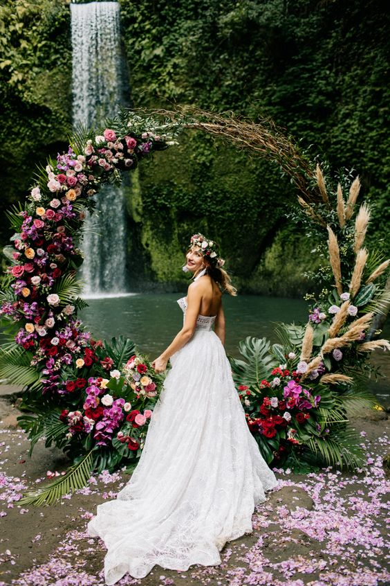a colorful round wedding arch with tropical leaves, pampas grass, bold red, pink and peachy blooms is wow