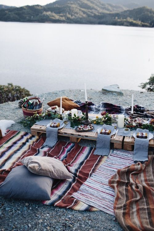 a cool lake picnic setting with a low table, colorful boho rugs, neutral candles and greenery and bright blooms