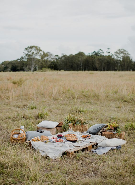 a cozy rustic picnic setting with a pallet table, stumps, baskets, neutral textiles, blooms and greenery