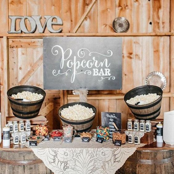 a cozy rustic popcorn bar with wooden baskets with popcorn, candies, sprinkles and toppings and chalkboard signage