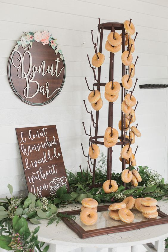a creative metal stand with hooks, lots of greenery and blooms, fresh donuts and a sign with calligraphy