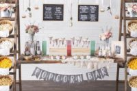 a creative popcorn bar with a couple of ladders and a door, popcorn in wooden baskets, chalkboard signs and paper cones and toppings on the door