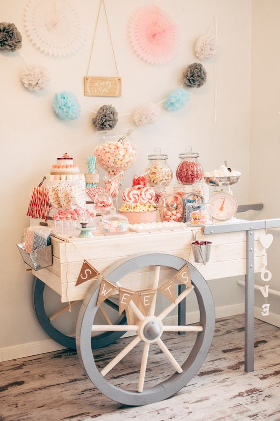 a cute vintage cart candy bar with banners, a sign, lots of tasty candies served in jars, on stands and in bowls