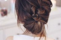 a diagonal braided updo with a low bun, some locks down and a little hairpiece