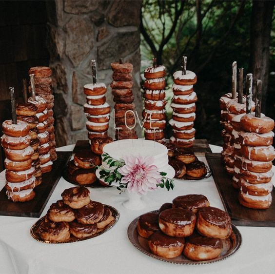 a donut station with donut son holders and metallic trays, a cake topped with fresh blooms and lots of delicious donuts