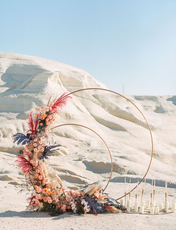 a fantastic wedding arch with pink and peachy blooms, dried grasses, pastel grasses and leaves plus candles on the ground
