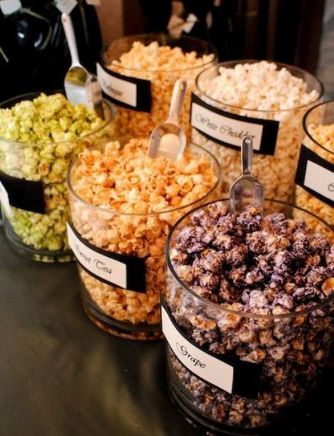 a flavored popcorn wedding bar with popcorn in glass jars and labels on them to mark the types