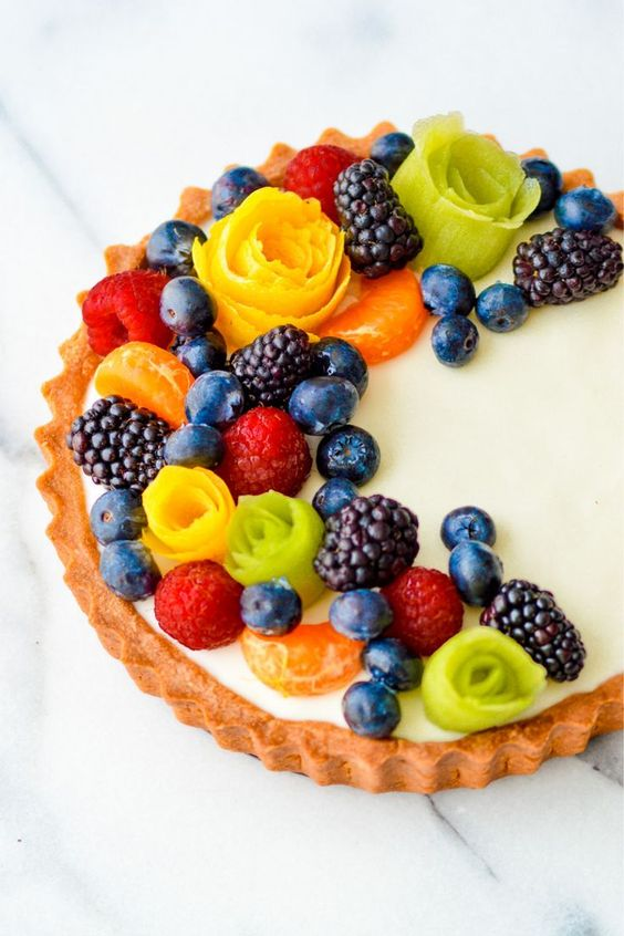 a fresh tartler with custard and blueberries, blackberries, raspberries, tangerines and flowers made of fruit