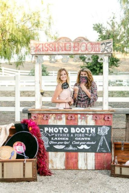a fun shabby chic kissing booth of wood, in pink and white, with a chalkboard sign and colorful props