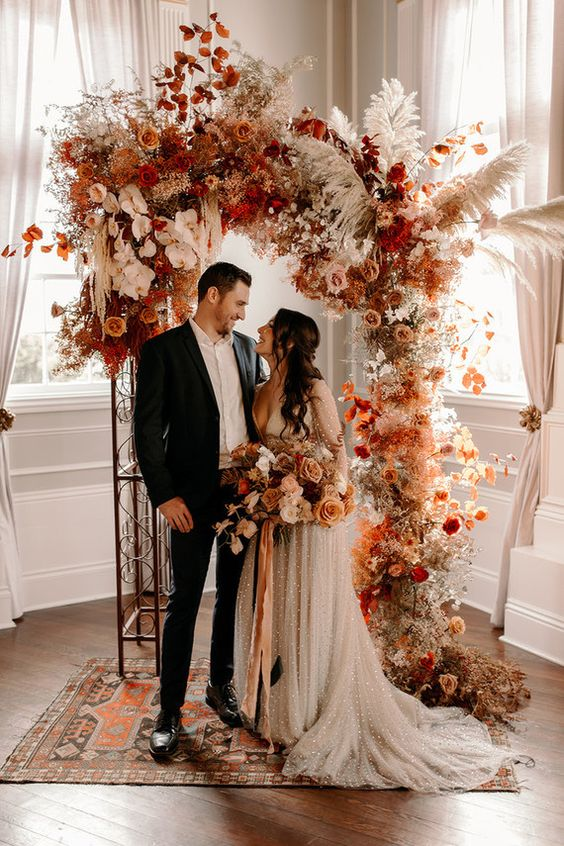 a gorgeous wedding arch with deep red, orange, rust, blush blooms, pampas grass, some foliage for a boho fall wedding