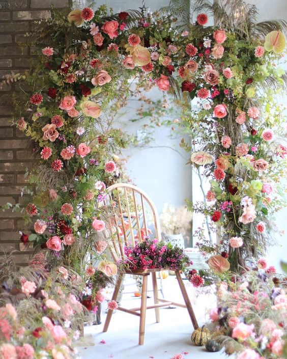 a gorgeous wedding arch with plenty of greenery, pink, red and blush blooms is a very beautiful and cool idea