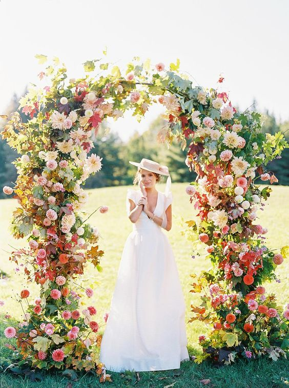a jaw-dropping wedding arch with some foliage, pink, blush, red and neutral blooms all over is amazing for a bright summer wedding