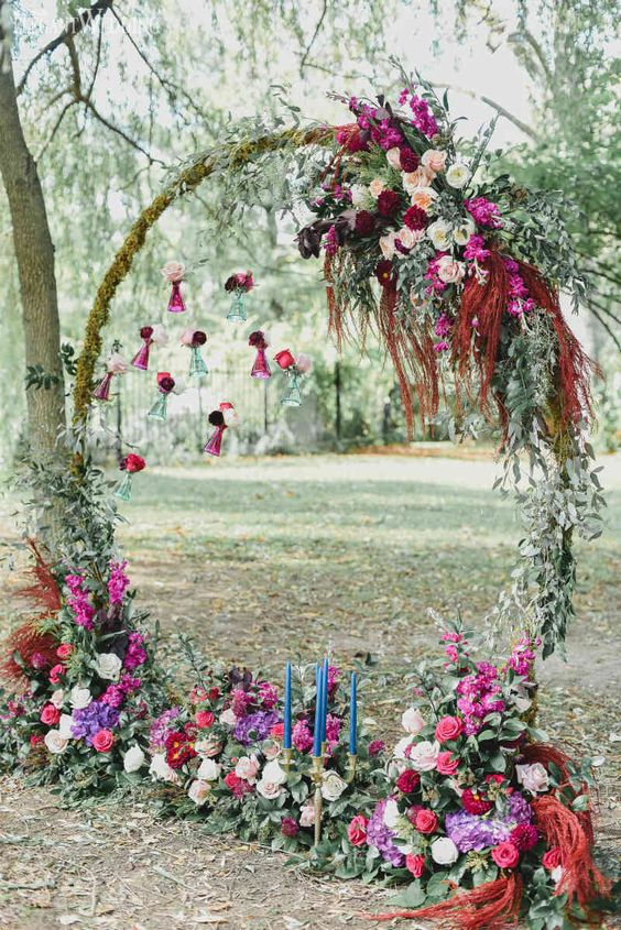 a jewel-tone round boho wedding arch with greenery, moss, blush, hot pink and purple blooms and blue candles in a gilded candleholder