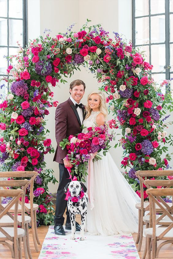 a jewel tone wedding arch with greenery, blush, hot pink and purple flowers is a gorgeous idea for a bold wedding