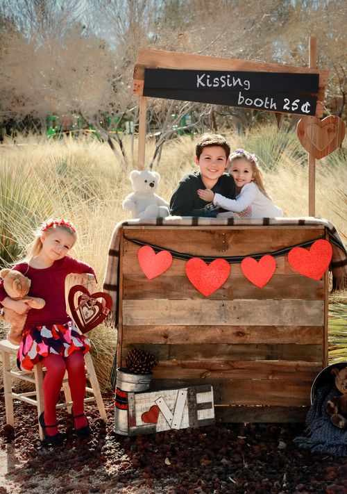 a kissing booth of pallets, with a heart bunting, a chalkboard sign, plush toys and blankets is a cute idea