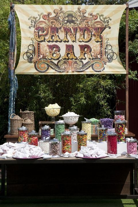 a large candy bar with a table, an oversized bright sign and lots of colorful candies in large jars