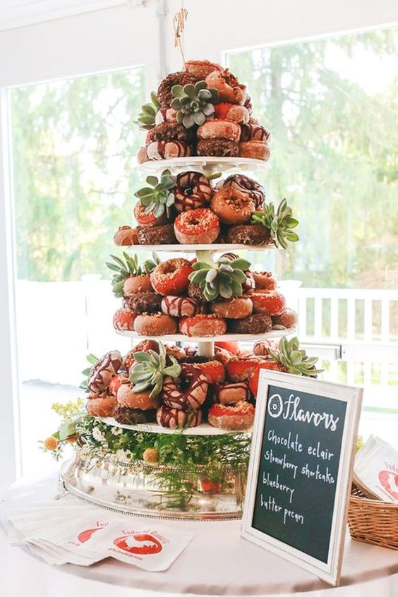 a large clear stand with lots of glazed donuts, and succulents and greenery plus a sign is your cool dessert table