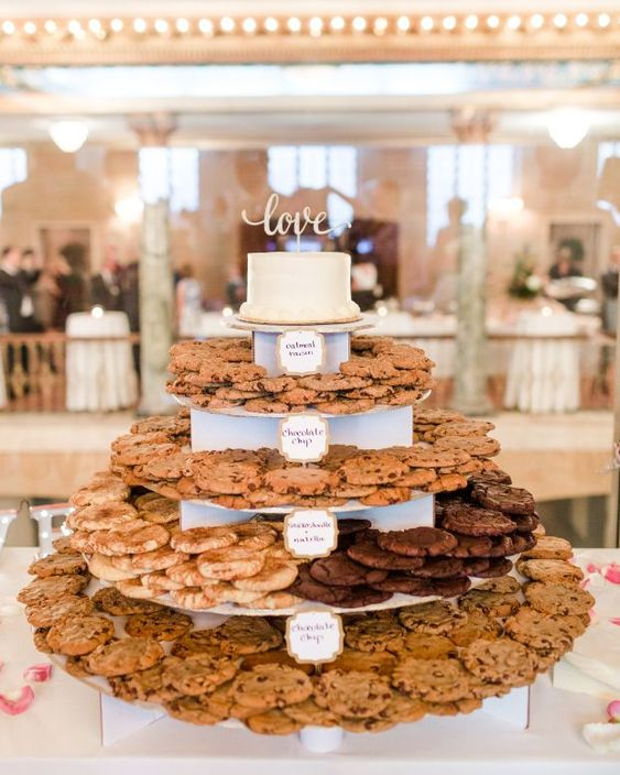 a large cookie stand with toppers and a wedding cake on top is a chic idea for any wedding