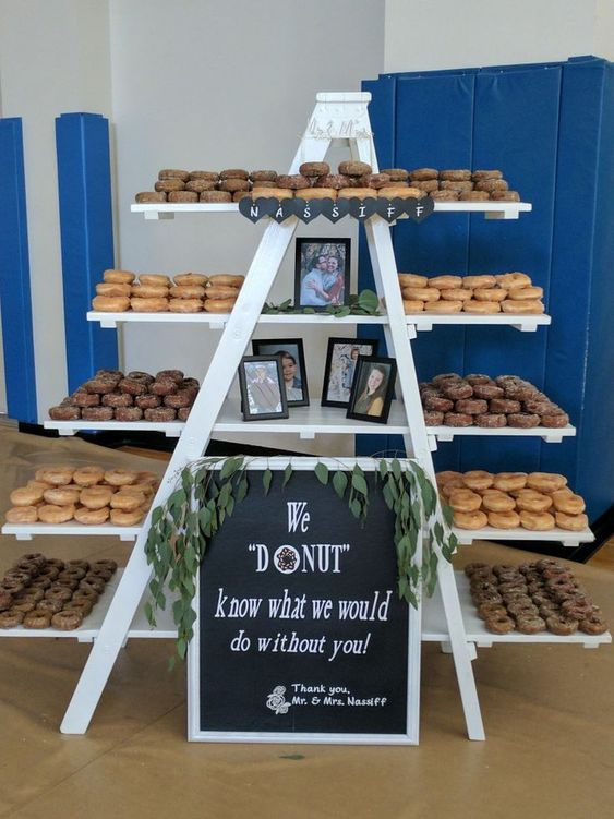a large donut table done with a ladder and shelves attached to it, with lots of donuts, photos and a sign