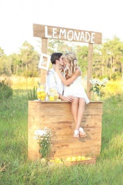 a lemonade kissing booth with white blooms and lemons in jars is ideal for a summer wedding
