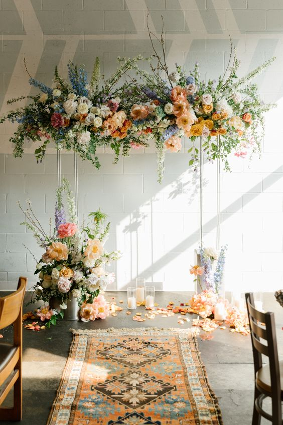 a lovely pastel wedding arch with white, orange, rusr, blue and pink blooms, blooming branches and greenery and candles on the floor for a spring wedding