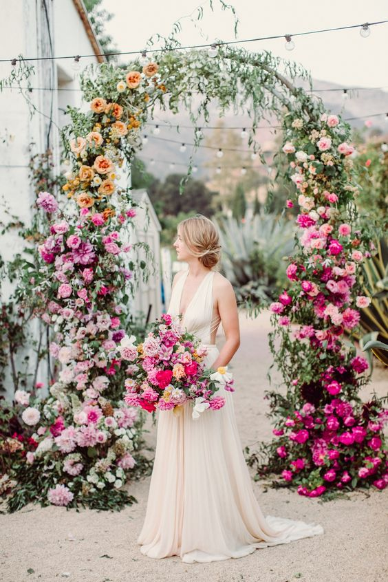 a lovely watercolor floral wedding arch with blush, orange, pink, white and hot pink blooms and greenery is wow