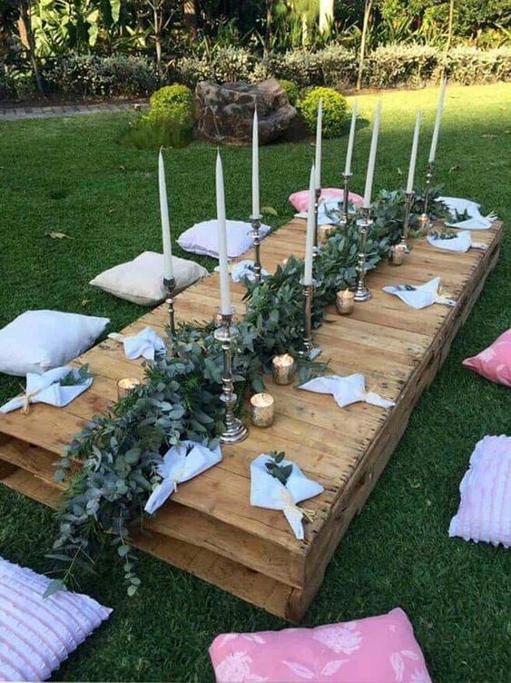 a low pallet table with a lush greenery runner, candles and white napkins plus neutral and pink pillows