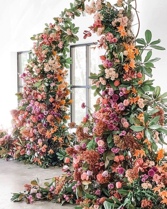a luxurious colorful wedding arch decorated with greenery, blush, hot pink, orange and rust-colored blooms is wow