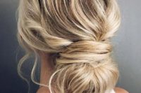 a messy and textural low bun with a bump and some locks down is a modern casual idea