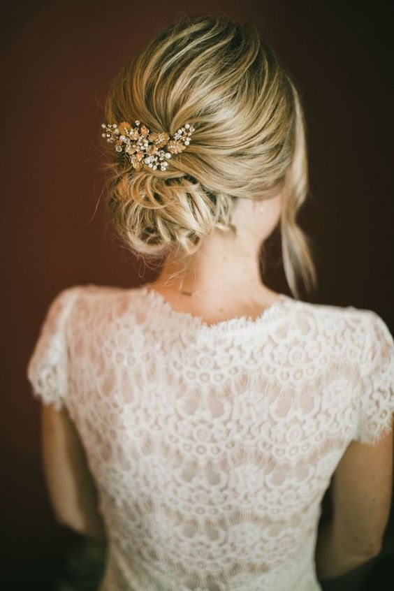 a messy low bun with a bump and a bead and rhinestone hairpiece plus some locks down