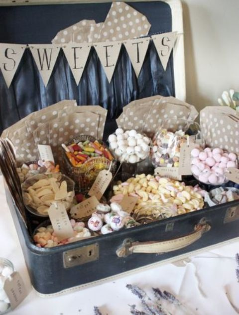 a mini candy bar of a vintage suitcase and jars and bowls with candies placed right inside, with paper bags and banners