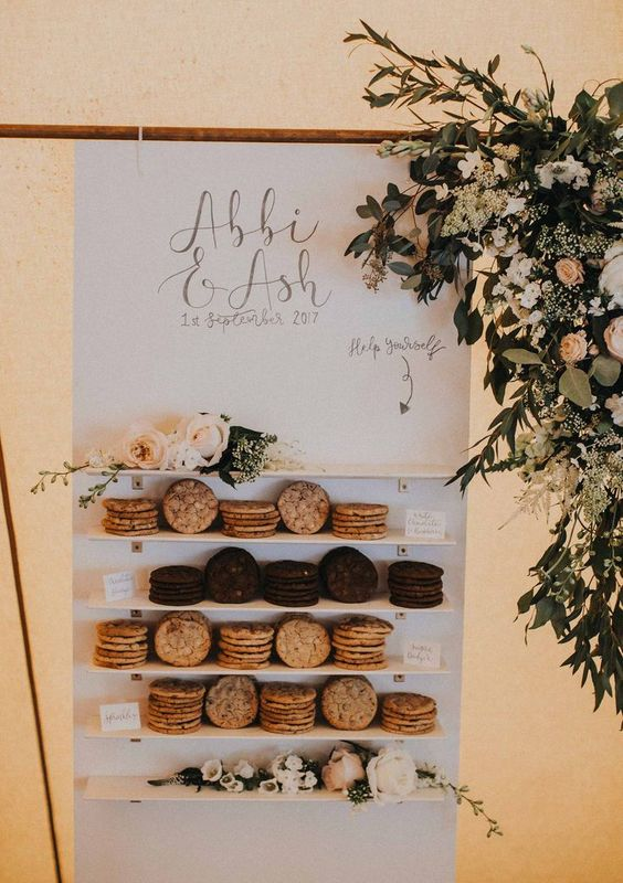 a mini cookie wall with various type sof sweets and fresh blooms and greenery for a romantic touch