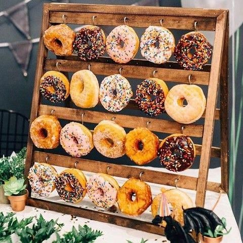 a mini wooden stand with metal hooks and glazed donuts is a super cute idea for a rustic wedding