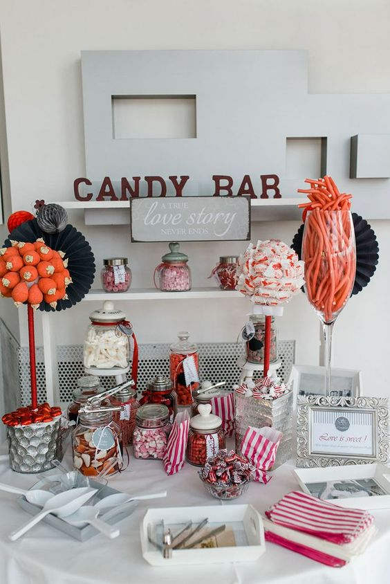 a modern neutral candy bar with a sign and letters, with bright candies in hars and bowls plus thongs to get them easily