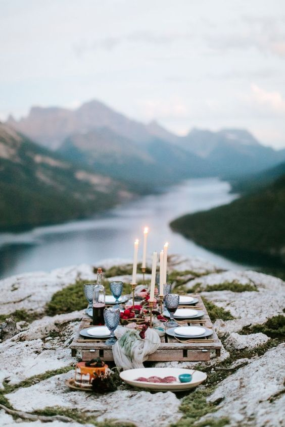 a mountain rehearsal dinner picnic with a pallet table, candles, blue glasses and porcelain plus a gorgeous view