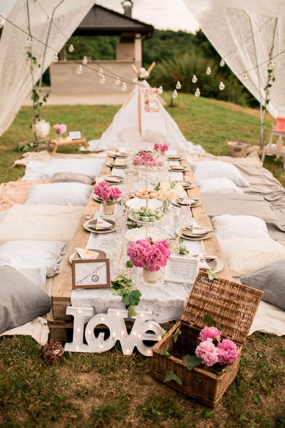 a neutral boho picnic setting with a low pallet table, neutral textiles, pink blooms, a LOVE sign and string lights over the table