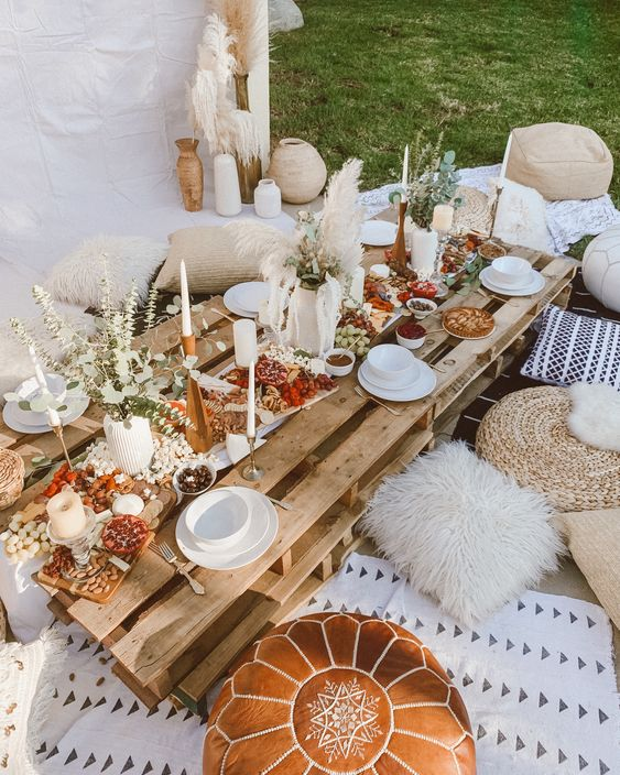 a neutral boho picnic  with a pallet table, printed blooms, rugs, greenery, pampas grasss and neutral textiles