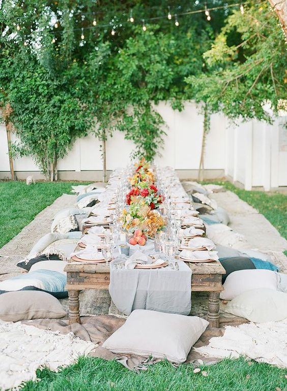 a neutrla garden picnic setting with a low wooden table, neutral textiles and bright blooms and greenery plus copper chargers