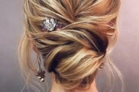 a pretty messy textural updo with a low twsited bun, locks down and a chic hairpiece