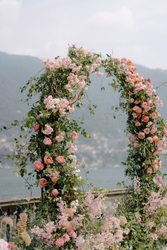 a refined and chic wedding arch with greenery, pink, blush blooms and blooms and greenery on the ground is beautiful