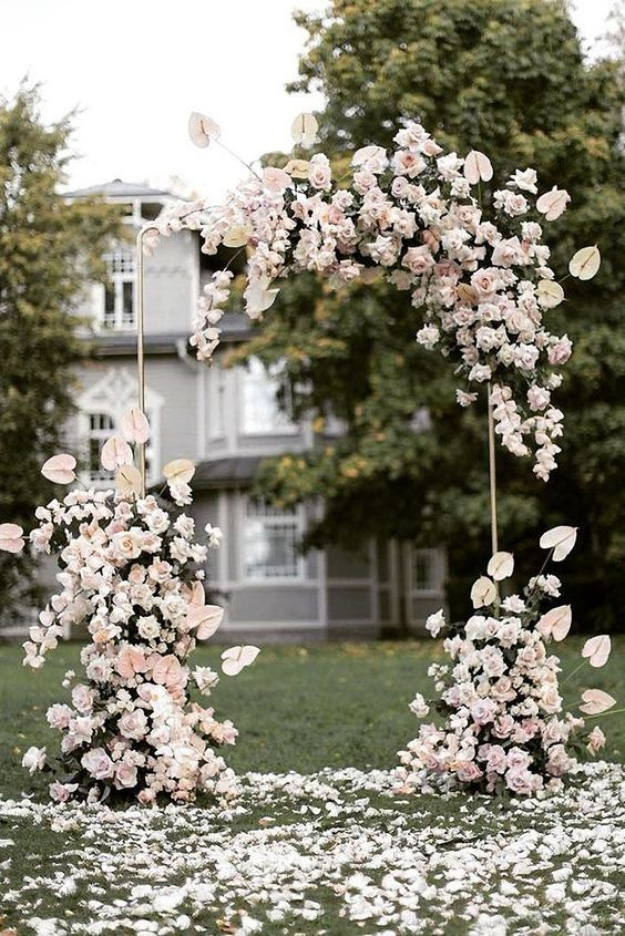 a refined and neutral wedding arch decorated with blush roses and with lush petals on the ground is wow