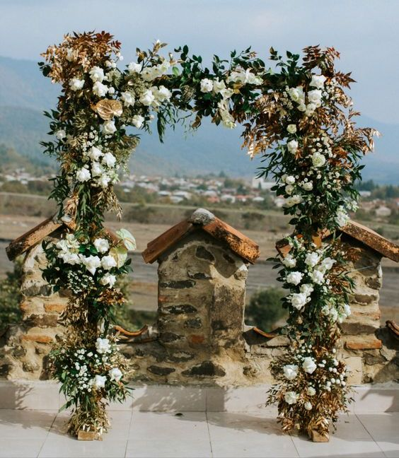 a refined wedding arch done with greenery, white blooms and dried bold foliage is a stylish idea for a fall wedding